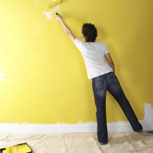 Man painting a wall yellow